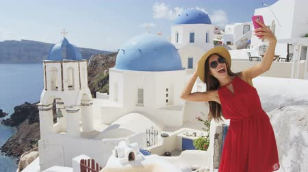 туристическим направлением : Woman taking phone selfie On travel in Oia, Santorini using smartphone by blue domed church. Female tourist sightseeing enjoying summer vacation visiting landmark destination in Greece, Europe