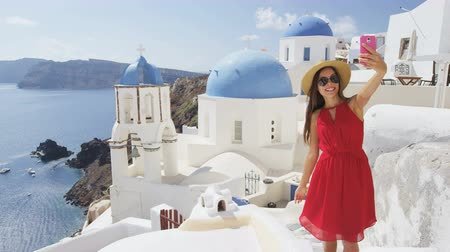 görögország : Woman taking phone selfie On travel in Oia, Santorini using smartphone by blue domed church. Female tourist sightseeing enjoying summer vacation visiting landmark destination in Greece, Europe