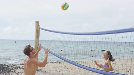 hareketli : People playing beach volleyball having fun in sporty active lifestyle. Man hitting volley ball in game in summer. Woman and man fitness model living healthy lifestyle doing sport on beach.
