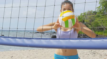 volleyball : Happy beach volleyball woman player. Fun Portrait of smiling woman throwing beach volley ball at net and looking at camera. Mixed race Asian Caucasian woman athlete Stock Footage