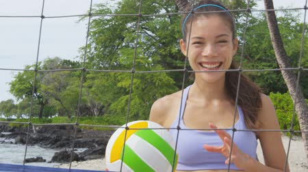 volleyball : Beach volleyball woman player. Fun Portrait of laughing woman throwing beach volley ball at net and looking at camera. Mixed race Asian Caucasian woman athlete