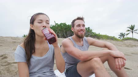 прессованный : Couple sharing beet juice on beach after exercise relaxing after workout running outdoor. Mixed race couple smiling happy together sitting relaxed enjoying healthy active living