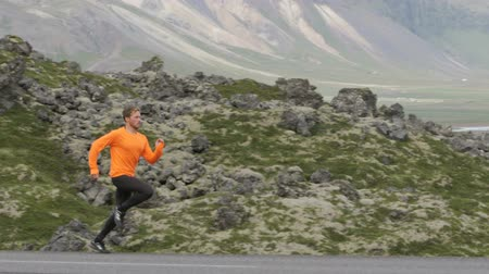 buty sportowe : Running sport man sprinting in slow motion on mountain road. Male runner exercising and training outdoors in beautiful mountains nature landscape on Iceland.