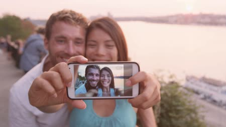 társkereső : Smart phone selfie - couple taking self portrait using smartphone camera. Dating couple in love having fun taking candid fresh picture photo laughing smiling. Caucasian man, Asian woman at sunset.