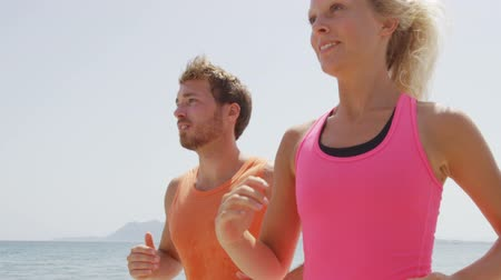 casal heterossexual : Running people workout. Slow motion video of young couple jogging by ocean. Man and woman are in sports clothing. They are representing their healthy lifestyle. Stock Footage