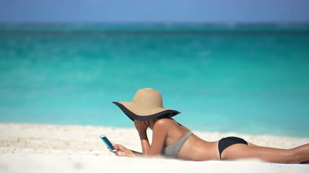 bronzeada : Woman using phone app on beach on summer travel vacation sunbathingon sand. Young female on smartphone lying on beach towel wearing sunhat by sea. She is wearing bikini while relaxing during summer. Vídeos