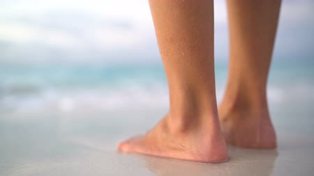 kipiheni magát : Close up of woman feet on beach. Girl getting her toes wet on vacation. Calm serene relaxing scene on with water splashing on feet in ocean on beautiful beach. Stock mozgókép