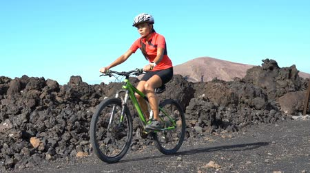 bicycle : Mountain biking MTB cyclist Person cycling on biking trail path. Woman mountain biker on bike in sportswear riding bicycle enjoying healthy active lifestyle in nature, Lanzarote, Canary Islands, Spain