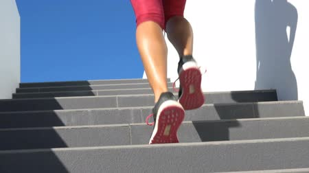 buty sportowe : Running on stairs woman doing run up on staircase. Female runner athlete climbing stairs in sport workout run outside. Running shoes and legs close up and zoom out. Wideo
