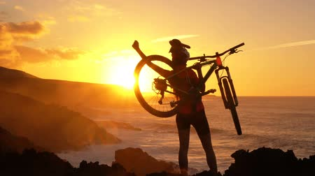 pico da montanha : Success, achievement, accomplishment and winning concept with cyclist mountain biking. Happy MTB woman cycling raising arms lifting bike by sea during sunset cheering and celebrating at summit top.
