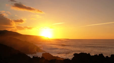 setting : Sunset of sun setting over atlantic ocean. Beautiful and colorful landscape showing dramatic sunlight and high waves hitting the scenic cliffs on the coast of Lanzarote, Canary Islands, Spain.