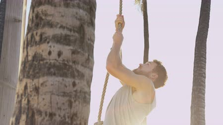сильный : Fitness man climbing rope exercising outdoor.  Male athlete adult on summer beach doing rope climb used in crossfit workout for strength training.