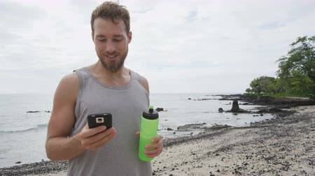 gotículas : Fitness man looking at phone app on beach. Running man using smartphone application resting relaxing with water bottle after workout exercise on beach outside. Mixed race Asian Caucasian girl. Stock Footage