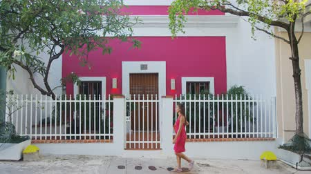kultúra : Woman walking in Streets of Old San Juan in Puerto Rico. Beautiful young mixed race woman in pink dress.