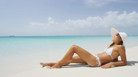 bronzlaşma : Sexy bikini body woman relaxing sun tanning on beach vacation lying down sunbathing on beach at tropical luxury destination in the Caribbean. Fashion, skincare solar protection, weight loss concept.