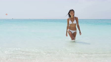 Sexy Asian bikini woman relaxing on beach walking out of turquoise ocean water wearing white fashion swimwear. Skin and hair care female model with slim body for weight loss or vacation concept.