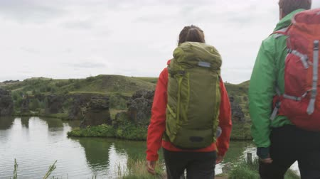 hiking : Hiking couple walking on hike by lake outdoors wearing backpacks trekking in beautiful nature landscape. Active young people living healthy lifestyle by Lake Myvatn, Iceland. RED EPIC STEADICAM. Stock Footage