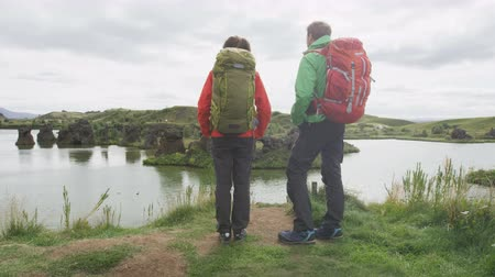 northern nature : People living healthy active lifestyle hiking. Aspirational young couple on hike looking at view of lake outdoors in beautiful nature landscape. Lake Myvatn, Iceland