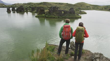 northern nature : Travel and hiking couple looking at view. People on hike by lake outdoors wearing backpacks trekking in beautiful nature landscape. Active young couple living healthy lifestyle by Lake Myvatn, Iceland