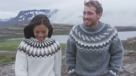 transportar : Happy young couple laughing outside in nature playful. Couple having fun on Iceland joyful and playful wearing Icelandic sweaters. Woman and man model enjoying nature landscape Stock Footage