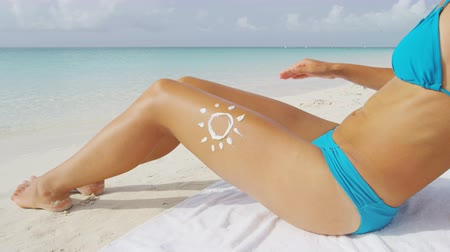 opalenizna : Beach woman applying sunscreen lotion on body - sun drawing skincare uv protection concept on sexy female bikini thigh leg closeup. Suntan person on Caribbean tropical vacation. Wideo