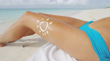 celulitida : Sunscreen sun care drawing in sunblock lotion. uv protection concept on sexy female bikini body thigh leg closeup. Suntan woman on the Caribbean beach tropical vacation.