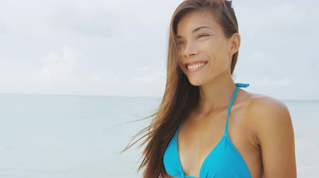 азиатский : Beautiful Asian bikini woman on tropical beach vacation with windy hair living a healthy lifestyle. Gorgeous fresh face model relaxing in the wind slow motion.