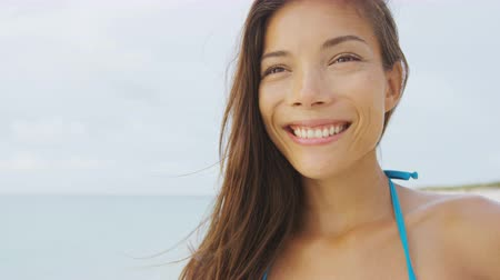 az egészséges életmód : Happy healthy bikini girl smiling on summer holiday beach vacation. Asian multiracial model with toothy smile relaxing on sunny tropical getaway. Mixed race face portrait. Stock mozgókép