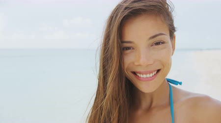 зубастая улыбка : Beach vacation Asian girl smiling a natural toothy smile. Happy healthy young ethnic mixed race brunette woman on beach vacation. Portrait of beautiful model looking at camera closeup.