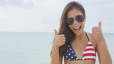 четверть : Cheering woman joyful doing fun thumbs up with US flag bikini on american beach vacation. Happy Asian girl celebrating USA stars and stripes pattern beachwear. Excited sexy model portrait smiling.