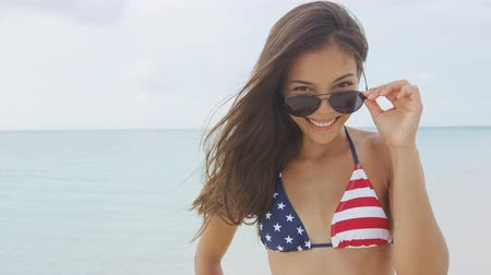 roupa de praia : Sexy beach woman wearing USA flag bikini flirting with sunglasses looking down at camera smiling on summer vacations holiday travel. Beautiful young multiethnic Asian Chinese in american wear.