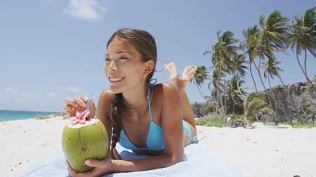 lefekvés : Happy beach bikini woman relaxing drinking fresh coconut water lying down sunbathing on fun Caribbean vacation tanning under the tropical sun. Asian model enjoying suntan. Stock mozgókép