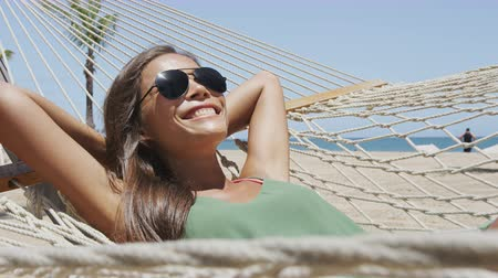 tonları : Summer vacation woman lying down on beach hammock putting on sunglasses relaxing sunbathing under the tropical sun resting on outdoor patio furniture swing bed at Caribbean resort. Stok Video