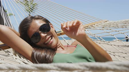 bronzlaşma : Happy beach girl tanning in aviator sunglasses relaxing in outdoor bed hammock saying hi waving hello at camera smiling happy during summer holidays. Asian woman on tropical destination getaway.