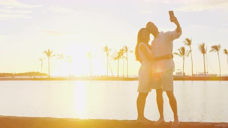 медовый месяц : Honeymoon couple taking selfie romantic at sunset in love enjoying vacation at beach using smart phone holding around each other in embrace on travel holidays getaway Стоковые видеозаписи