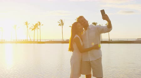 медовый месяц : Vacation travel couple taking selfie photo romantic at sunset in love at beach using smart phone holding around each other in embrace on honeymoon holidays getaway. Man, woman. Big Island, Hawaii, USA Стоковые видеозаписи