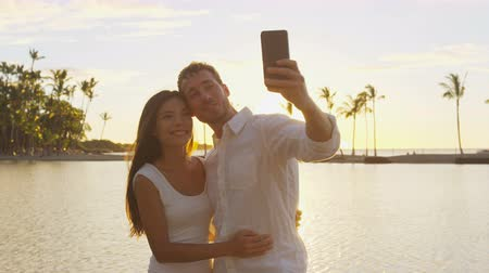 медовый месяц : Selfie couple romantic at sunset on vacation travel taking photo in love at beach using smart phone holding around each other in embrace on honeymoon holidays getaway. Man and woman
