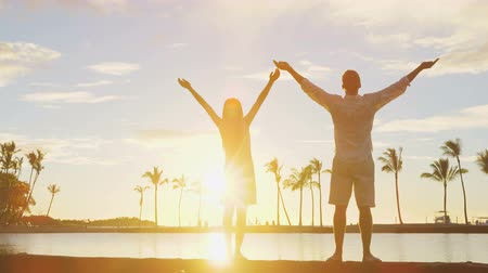 наслаждаться : Serene happy couple enjoying nature sunset raising arms to the sky enjoying freedom and wellbeing feeling bliss and freedom. Woman and man enjoying amazing sunset together.
