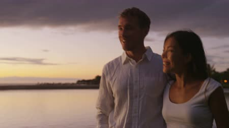 медовый месяц : Honeymoon couple romantic at sunset walking in love enjoying vacation at night talking together laughing in casual clothing at beach lagoon on Big Island, Hawaii, USA. Interracial couple.