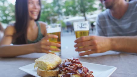 madryt : Couple eating tapas drinking beer in Madrid, Spain. Romantic man and woman enjoying local traditional food on square in Madrid. Asian woman and Caucasian man dating. Focus on beer and food. Wideo