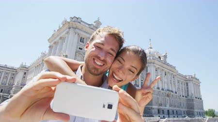 palacio real : Couple taking selfie photo on smartphone in Madrid. Romantic man and woman in love using smart phone to take self-portrait photograph on travel in Madrid, Spain by Palacio Real de Madrid. Stock Footage