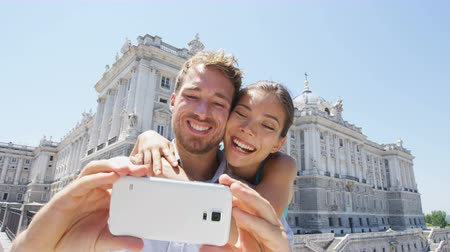фотографий : Vacation couple taking selfie photo on smartphone in Madrid. Romantic man and woman in love using smart phone to take self-portrait photograph on travel in Madrid, Spain by Royal Palace. Стоковые видеозаписи