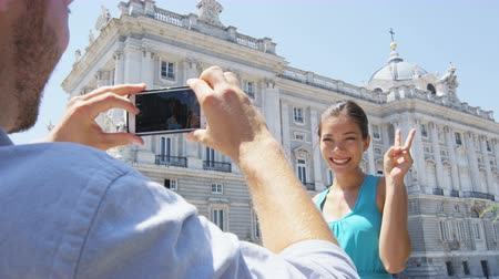 palacio real : Tourists taking photo on smart phone in Madrid. Romantic couple man and woman in love using smartphone taking photograph on travel in Spain by Palacio Real de Madrid