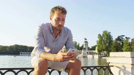telefone celular : Man sms texting using app on smart phone at sunset in city park. Handsome young business man using smartphone smiling wearing shirt outdoors in el Retiro in Madrid, Spain, Europe. Urban professional. Stock Footage