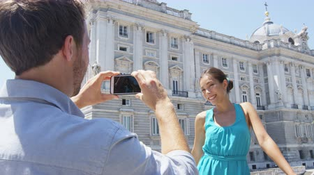 palacio real : Couple tourists taking photo on smart phone in Madrid. Romantic man and woman in love using smartphone taking photograph on travel in Spain by Palacio Real de Madrid