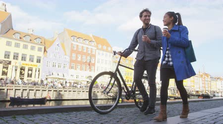 kodaň : Copenhagen people. Couple walking in Nyhavn, old port. Famous tourist attraction destination in Denmark Young multiracial happy couple with bicycle bike and coffee Dostupné videozáznamy