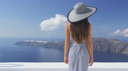 Travel vacation woman looking at view on Santorini famous Europe tourist destination. Elegant young lady living fancy jetset lifestyle wearing dress on luxury holidays. Amazing view of sea and Caldera