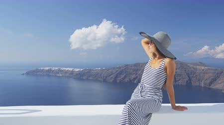 УВР : Vacation woman enjoying sun elegant on luxury travel on Santorini, famous Europe travel destination. Young lady living fancy jetset lifestyle wearing dress on holidays. Amazing view of sea and Caldera Стоковые видеозаписи