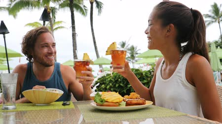 namoro : Couple dating having fun drinking alcohol at beach club with alcoholic drink beverage Mai Tai cocktail on Hawaii. Portrait of romantic young mixed race couple on honeymoon romance on Hawaiian beach.