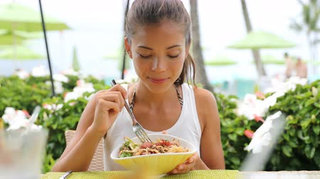 тыкать : Woman eating a fresh raw tuna dish, hawaiian local food poke bowl, at outdoor restaurant table during summer travel vacation. Hawaii poke bowl food plate. Ahi tuna hawaiian cuisine. 59.94 FPS.